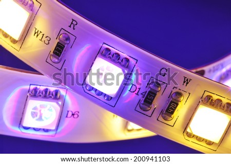 macro detail of a RGBW-LED-stripe with warmwhite LEDs in colored spotlight  - stock photo