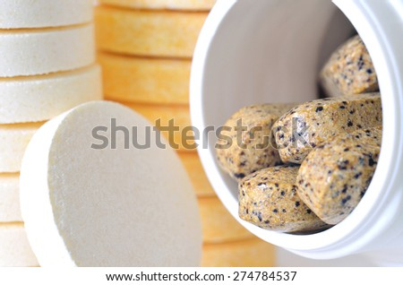 Macro detail of bottle of multivitamin supplement pills and soluble vitamine C tablets in foreground - stock photo