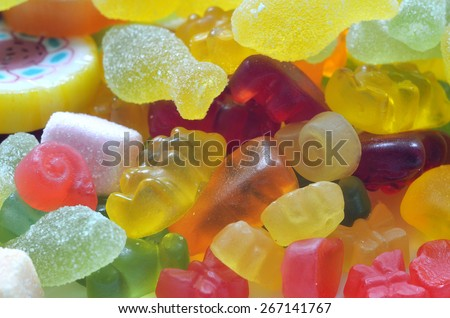 Macro detail of lollipop, gummy bears and sour candy on colored smarties background - stock photo