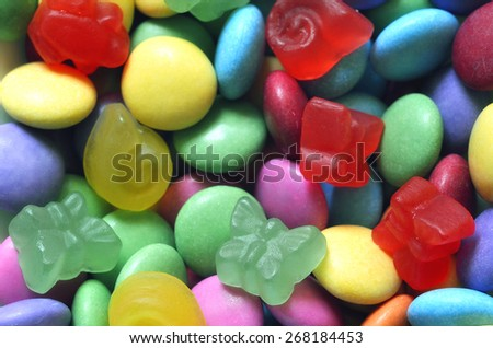 Macro detail of pile of colored smarties and candy shaped like butterfly background - stock photo