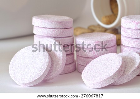 Macro detail of soluble magnesium tablets and bottle of multivitamin supplement pills in foreground - stock photo