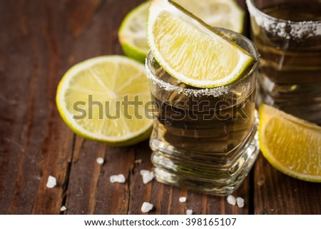 Macro focus photo of shots of golden Mexican tequila with lime and salt on wooden  background. Alcoholic drink concept.  - stock photo