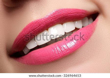 Macro happy woman's smile with healthy white teeth, bright pink .lips make-up. Stomatology and beauty care. Woman smiling with great teeth. Cheerful female smile with fresh clear skin - stock photo