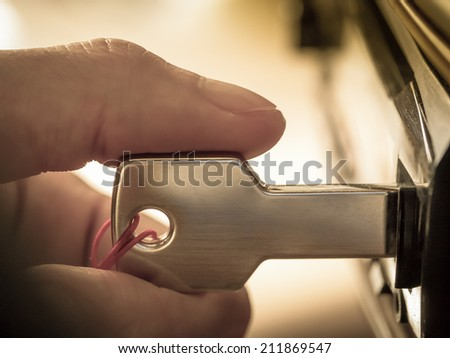 Macro image of a hand plugging key-shaped USB drive into car audio in concept of mobile entertainment technology - stock photo