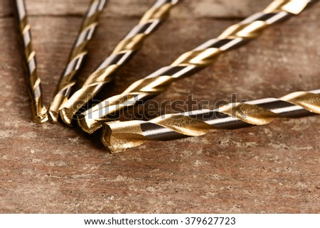 Macro image of Drill bits for concrete of different sizes on wooden desk. - stock photo