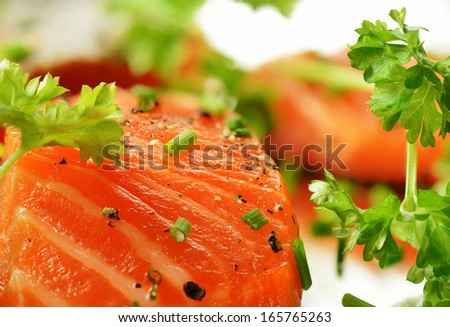 Macro image of fresh salmon fillet with garnish and cracked black pepper. Copy space. - stock photo