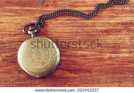 macro image of old vintage pocket watch on wooden table. top view. retro filtered image - stock photo