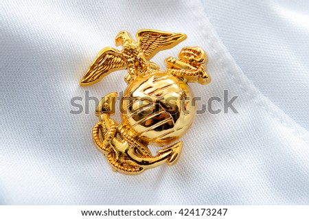 Macro image of the US Marine Corps emblem on a white glove used as background - stock photo