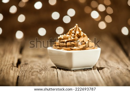 Macro Mouth Watering Brown Frozen Yogurt on Bowl Placed on Wooden Table - stock photo