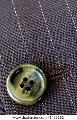 Macro of a buttonhole in a businessman's pin-stripe suit. Texture and light. - stock photo