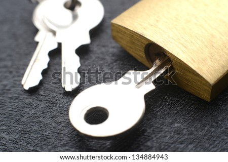 Macro of a locked padlock with the key on it - stock photo