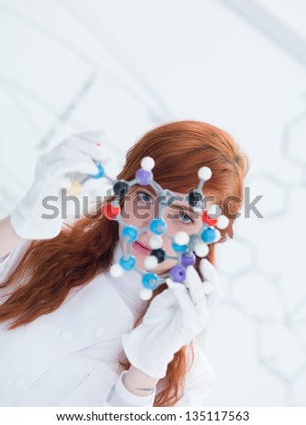 macro of a student in a chemistry lab holding in hands and analyzing DMT molecular model and a white board on the background - stock photo