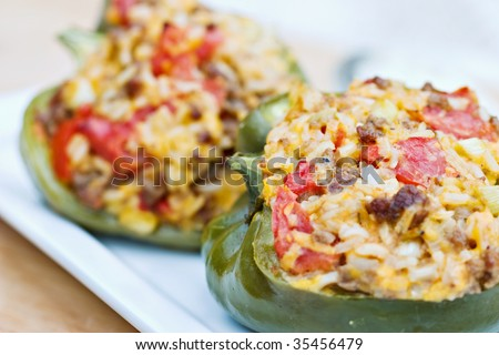 Macro of baked peppers stuffed with turkey burger, rice, tomatoes and cheddar cheese. Shallow DOF with focus on pepper in front. - stock photo