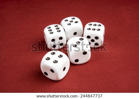 Macro of five dice on cloth red surface with shallow depth of field focusing on the front dice - stock photo
