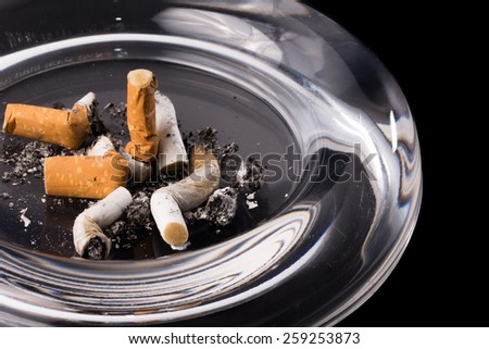 Macro of glass ashtray stand cigarette in detail - stock photo