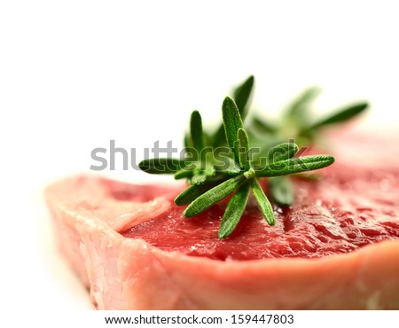 Macro of juicy sirloin steak with fresh sprigs of rosemary garnish. Shallow depth of field against a white background. Copy space. - stock photo