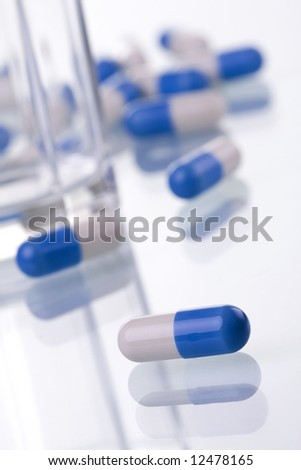 macro of pills and a glass (selective and soft focus) - stock photo