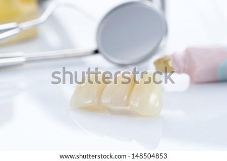 Macro of prosthetic teeth with dental tools - stock photo