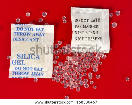 Macro of silica gel bags on red background - stock photo