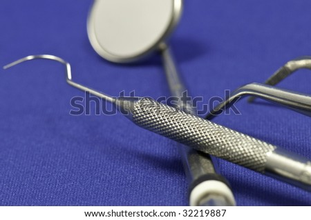 Macro of the dentist instruments on a blue background. - stock photo