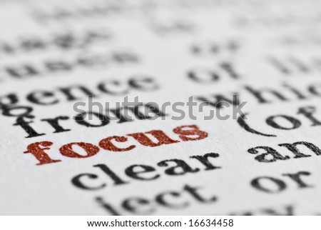 Macro of the word focus in the dictionary, with entire image in black and white apart from the word focus, which is in red - stock photo