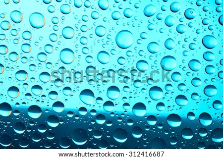 Macro of water drops on blue background - stock photo
