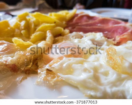 macro of white dish with typical Spain food named huevos rotos or broken eggs with potatoes french fries fried eggs and slices of iberico iberian ham on table at cafe restaurant - stock photo