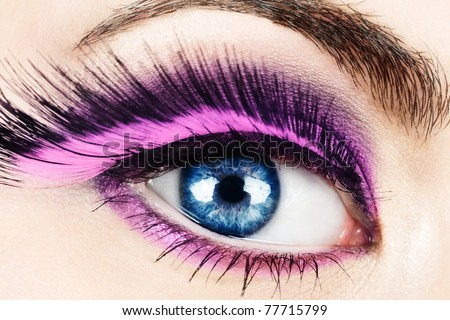 Macro of woman's eye with long pink feather fake eyelashes. - stock photo