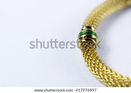 macro or close up three green emerald stone in a golden jewelry with white background.  - stock photo