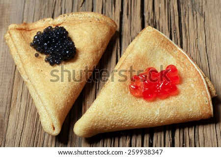 macro pancakes with caviar on a background of an old tree studio - stock photo