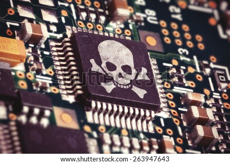 Macro photo of a circuit board with microchip carrying a pirate symbol - stock photo