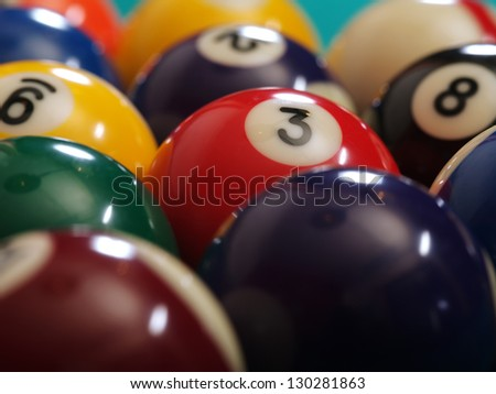 Macro photo of a pool table and billiard balls. Shallow depth of field with focus on the three ball. - stock photo