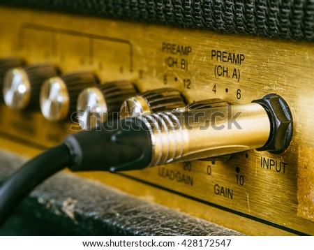 Macro photo of a vintage electric guitar amplifier showing the knobs and input plug. Selective focus on the word input. - stock photo
