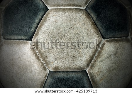 Macro photo of an old black and white soccer ball with hexagons and pentagons in leather - stock photo