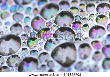 Macro photo of colorful soap bubbles on the water - stock photo
