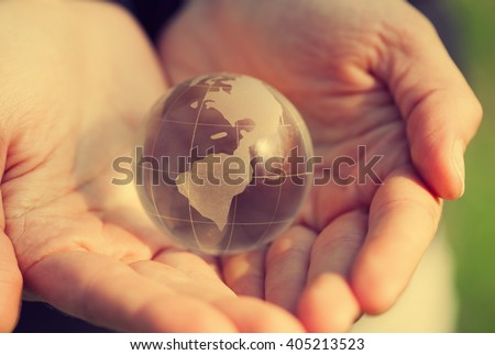 Macro photo of human holding a crystal glass globe model. Concept for peace, love and unity.  - stock photo