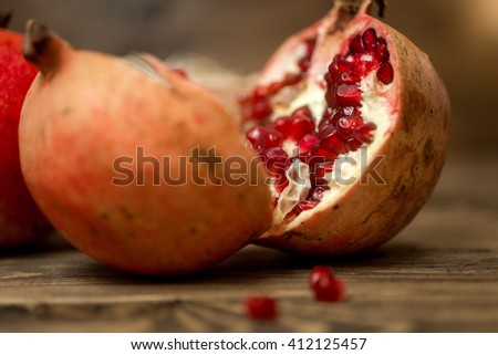Macro photo of pomegranate two halves lying on old wooden desk - stock photo