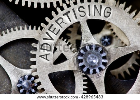 Macro photo of tooth wheel mechanism with ADVERTISING concept words - stock photo