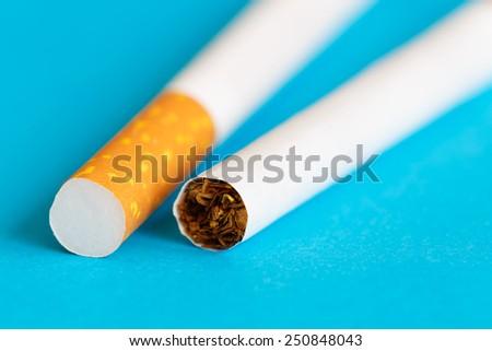 Macro photo of two cigarettes on blue background - stock photo