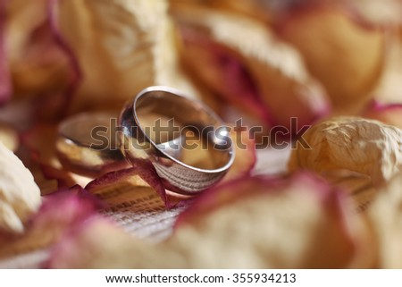 Macro photo of two wedding rings among dried rose petals on the table. The symbol of a happy marriage and love - stock photo