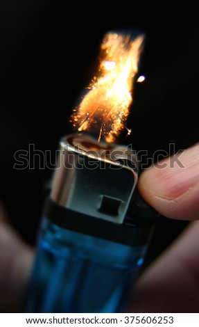Macro photograph of a cigarette lighter at the moment of ignition, just as the flame catches fire. - stock photo