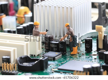 Macro photograph of a computer motherboard and two tiny toy engineers fixing something, concept. - stock photo