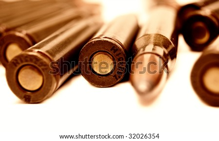 Macro set of Kalashnikov AK-47 (7,62 mm) cartridges (shallow DOF) on white background. Live ammunition for automatic weapon closeup toned image selective focus - stock photo