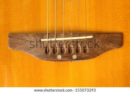 Macro shot down the fretboard of acoustic guitar - stock photo