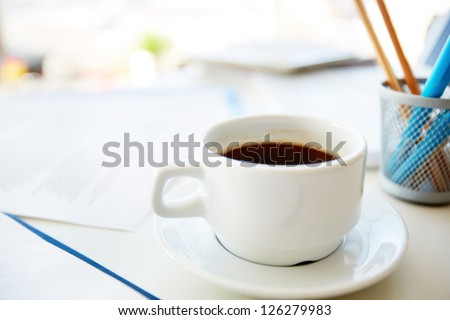 Macro shot of a coffee cup standing on the office desk - stock photo