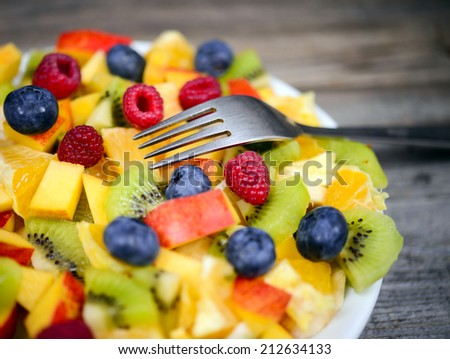 Macro shot of a fresh fruit salad with bananas kiwi orange blueberries and peach with fork - stock photo