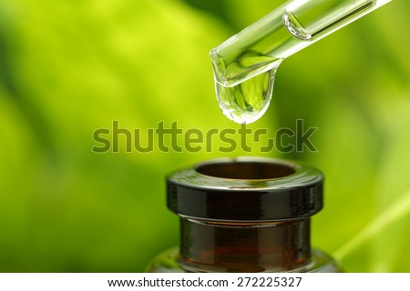 Macro shot of a pipette over a bottle, with fresh foliage in the background.  - stock photo