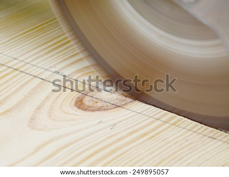 Macro shot of a saw blade cutting a pine wood board - stock photo