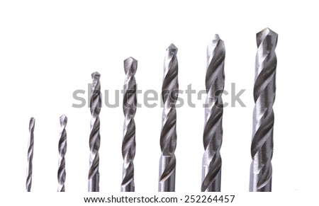 Macro shot of a set of small drill bits on a white background - stock photo