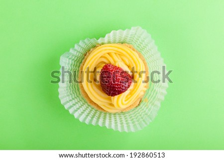 macro shot of a strawberry with custard over a green background - stock photo